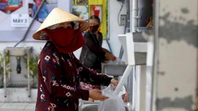 Seorang wanita di Vietnam mengisi kantong dengan beras dari mesin ATM beras gratis yang beroperasi selama 24 jam