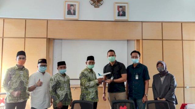 Penyerahan cinderamata Ketua PCNU Kota Makassar, KH Kaswad Sartono kepada Vice President Kalimantan Sulawesi Papua PT Garuda Indonesia Berthon Hutapea (Foto: Ist)