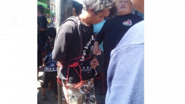 Pelaku pembakar mimbar Masjid Raya Makassar, Sulawesi Selatan ditangkap dan diikat di tiang telepon. (Foto/iNews TV)