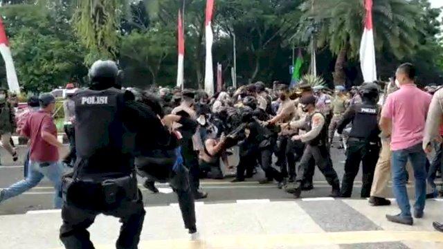 Seorang polisi membanting mahasiswa HIMATA Banten Raya saat terjadi kerusuhan demonstrasi, Rabu 13 Oktober 2021.